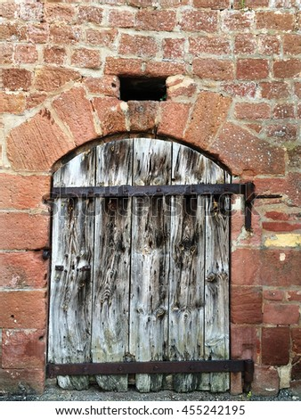 Medieval wall with wooden door - stock photo