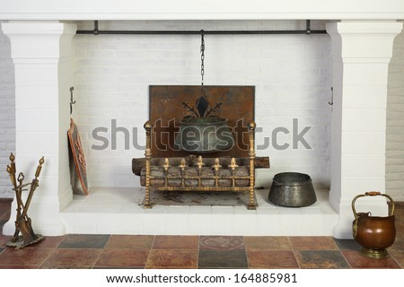 Medieval white fireplace with hanging metal pot and logs in studio. - stock photo