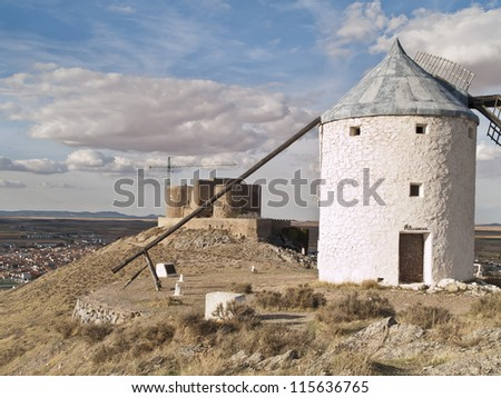 Medieval windmill on a hill overlooking the town of  Consuegra in Toledo province, Spain. They dating from the 16th century . Castle at the background. - stock photo