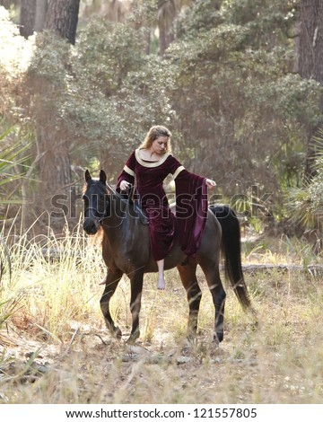 medieval woman in formal dress riding horseback through forest - stock photo