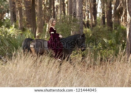 medieval woman riding horse through forest - stock photo