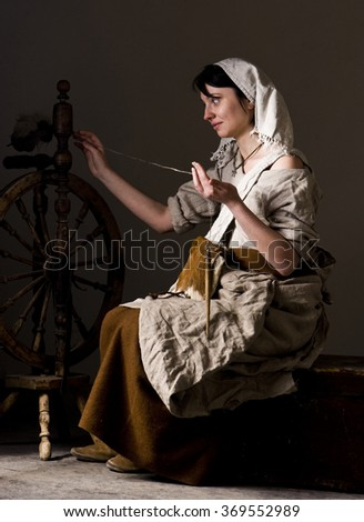 Medieval woman. Woman spinning on the great or walking wheel - stock photo
