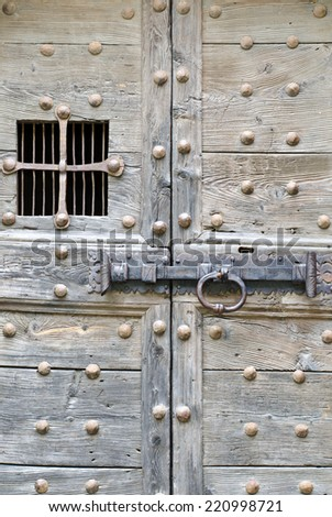 Medieval wooden door with iron handle and window - stock photo
