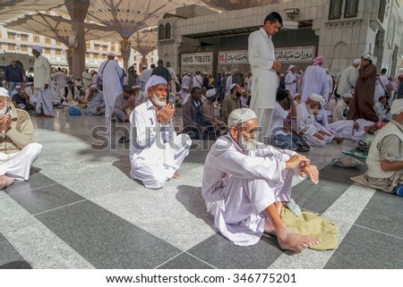 MEDINA, KINGDOM OF SAUDI ARABIA (KSA) - JAN 31: Pilgrims pray outside Masjid Nabawi after morning prayer Jan 31, 2015 in Medina, KSA. The mosque is the second holiest mosque in Islam.