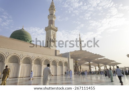 MEDINA, KINGDOM OF SAUDI ARABIA (KSA) - MAR 06: Muslims marching in front of the mosque of the Prophet Muhammad on March 06, 2015 in Medina, KSA. Prophet's tomb is under the green dome.  - stock photo