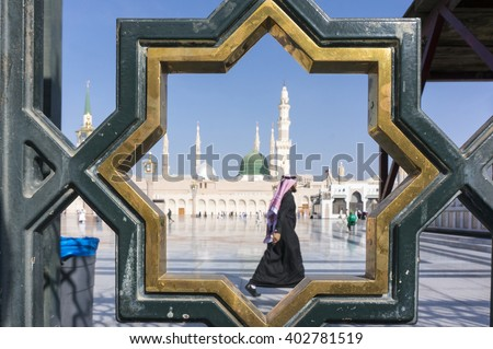 MEDINA, SAUDI ARABIA-DECEMBER 18, 2014: Unidentified Arab muslim walks on the compound of Nabawi Masjid (mosque) in Medina, Kingdom of Saudi Arabia. - stock photo