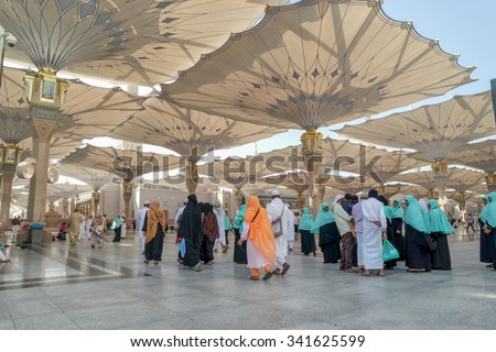MEDINA, SAUDI ARABIA-JAN 30: Muslims from different countries in the courtyard of the mosque of the Prophet on January 30, 2015 in Medina, KSA. The Nabawi mosque is the second holiest mosque in Islam. - stock photo
