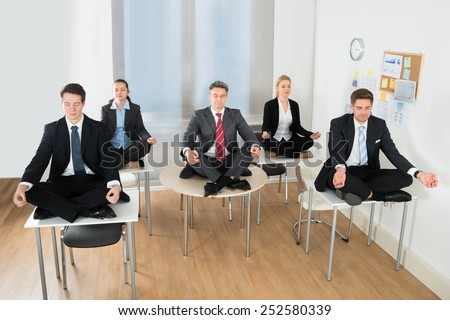 Meditating Businesspeople Sitting On Desk With Their Legs Crossed In Office