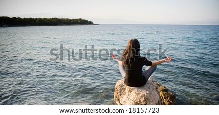 Meditating by the sea - stock photo