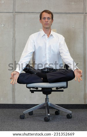 meditating caucasian businessman in lotus pose on office chair - stock photo