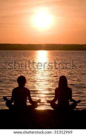 Meditating couple sitting in pose of lotus during wonderful sunset - stock photo