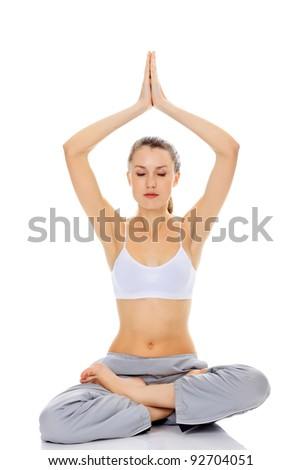 meditating girl sitting on a white floor - stock photo