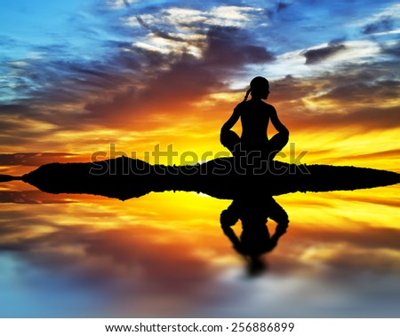 meditating in front of the sun - stock photo