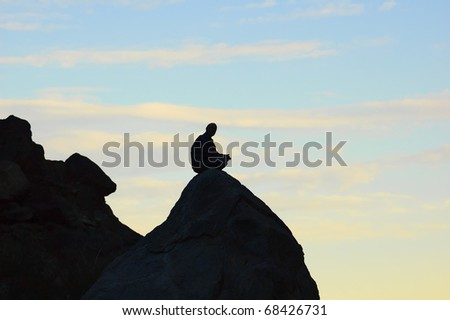Meditating man sitting on top of a rock in the mountains - stock photo