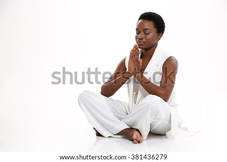 Meditating pretty african american young woman sitting in yoga pose with legs crossed over white background - stock photo
