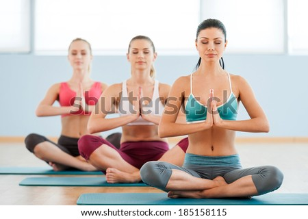 Meditating together. Three beautiful young women in sports clothing holding hands clasped and keeping eyes closed while sitting at lotus position - stock photo