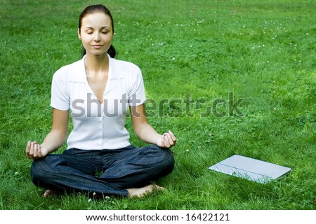 Meditating woman with laptop - stock photo