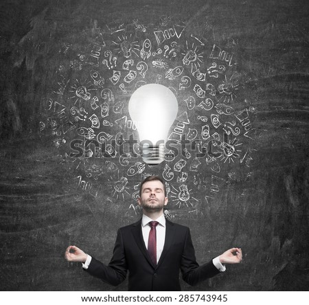 Meditating young businessman thinking about the light bulb. A concept of the brainstorm in business development.