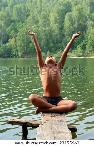 meditation asian boy on stage near lake - stock photo