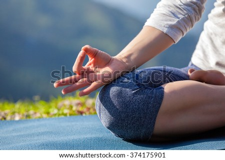 Meditation healthy life exercise concept - Close up of woman in Padmasana yoga lotus pose with chin mudra outdoors with copyspace - stock photo