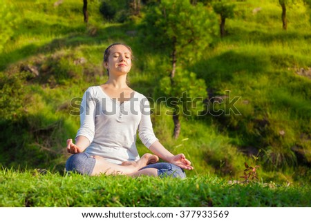 Meditation healthy life exercise concept - Young sporty fit woman doing yoga outdoors - meditating and relaxing in Padmasana Lotus Pose) with chin mudra on green grass in forest - stock photo