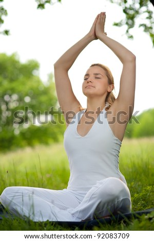 Meditation in nature - Cute young girl meditates outdoor on a green grass field in park - stock photo