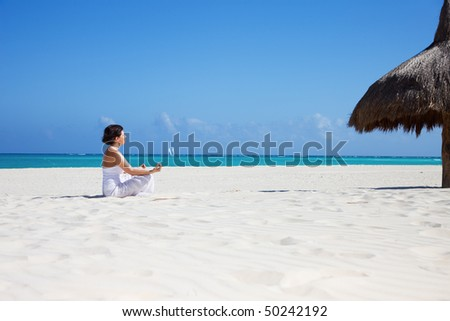 meditation of happy woman in lotus pose on the beach - stock photo