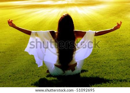 Meditation on a green field in solar beams - stock photo