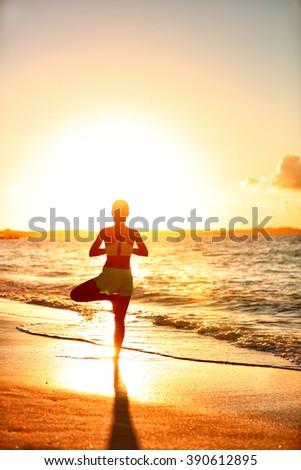 Meditation woman practicing Vriksasana tree yoga pose on beach at sunset. Serene young adult silhouette in morning sun flare balancing meditation doing a body workout. Wellness concept. - stock photo