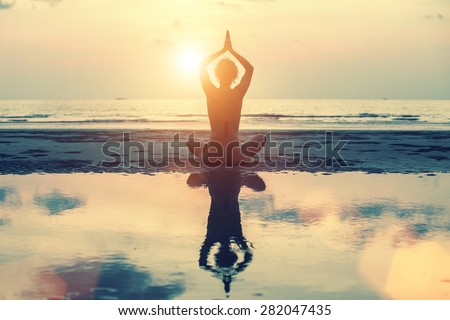 Meditation, yoga and fitness, a healthy lifestyle. Silhouette of a beautiful yoga woman at sunset in surreal colors.  - stock photo