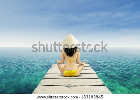Meditation - Yoga woman meditating at serene beach - stock photo