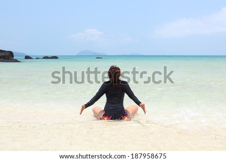Meditation - Yoga woman meditating at serene beach sunset. Girl relaxing in lotus pose in calm zen moment in the ocean water during yoga holidays resort retreat. Multiracial girl.  - stock photo