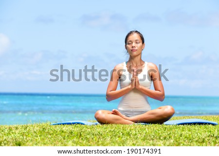 Meditation yoga woman on beach meditating by ocean sea sitting in lotus position with back turned serene and happy. Asian girl sitting relaxing enjoying summer beach. Mixed race Asian Caucasian model. - stock photo