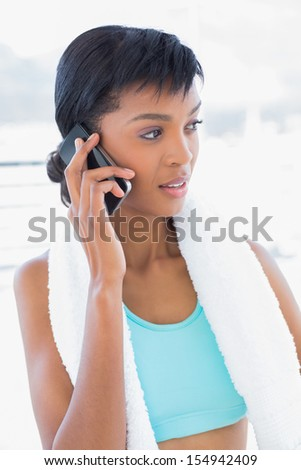 Meditative black haired woman phoning in a living room