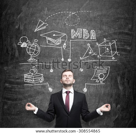 Meditative businessman is going to get the master's degree in business administration. A concept of the MBA degree. Drawn educational icons on the chalkboard. - stock photo