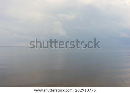 Meditative calm on the Baltic Sea with a red and blue buoy horizon  - stock photo