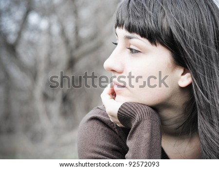 Meditative young brunette outdoors - stock photo