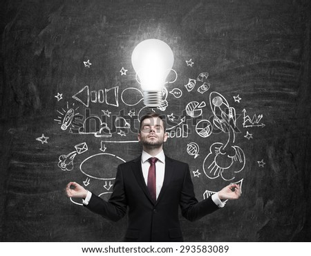 Meditative young businessman is looking for new business ideas. Drawn business icons on the black chalk board and a light bulb as a concept of new idea. - stock photo