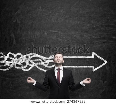 Meditative young businessman is trying to find the best solution for business development. An arrow as a symbol to the fast way of the implementation of the innovative ideas. Chalk wall background. - stock photo