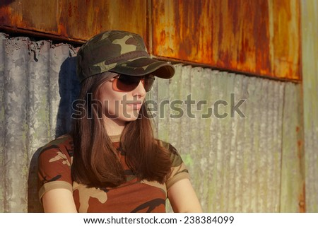 Meditative Young Woman Soldier in Camouflage Outfit Portrait of a tough beautiful female army soldier  - stock photo
