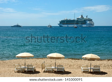Mediterranean beach with three umbrellas in Cannes, France - stock photo
