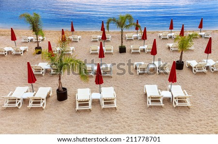 Mediterranean beach with white sunbeds and red umbrellas - stock photo