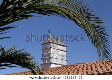 mediterranean chimney with palm tree. - stock photo