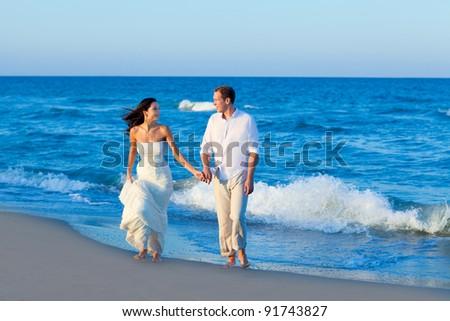 Mediterranean couple walking in blue beach shore - stock photo