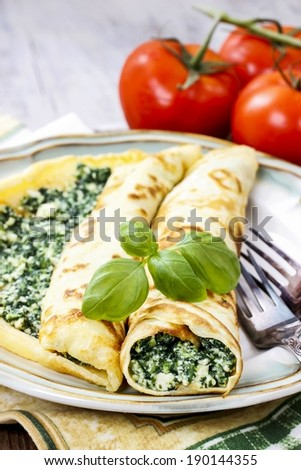 Mediterranean cuisine: crepes stuffed with cheese and spinach - stock photo
