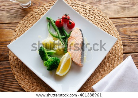 Mediterranean cuisine dish. Salmon steak and steamed vegetables, served on a wooden background. Lenten  healthy Mediterranean cuisine food. Top view on dietary fish dish with salmon and vegetables - stock photo