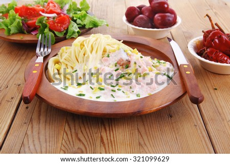 mediterranean cuisine: fresh rose wild salmon baked in cream cheese sauce with italian pasta and red hot pepper on wooden dish over table with vegetable salad - stock photo