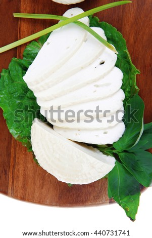 mediterranean cuisine : raw soft feta white cheese round with slices on wooden plate isolated over white background - stock photo