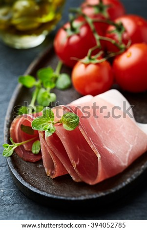 Mediterranean cured ham with cherry tomatoes on a rustic plate - stock photo