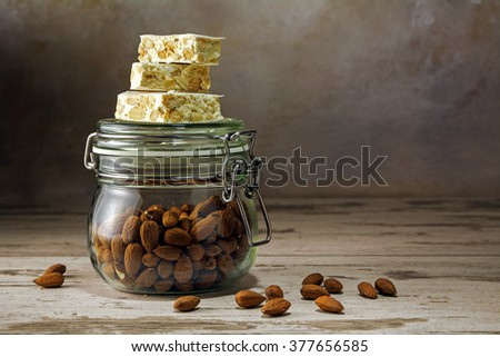 mediterranean festive torrone or nougat on a glass jar with almonds on a rustic woodn table, copy space, selected focus, narrow depth of field - stock photo